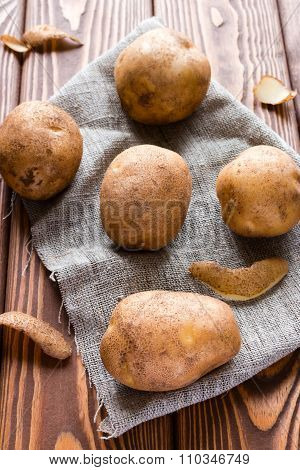Unpeeled Potatoes On A Gray Napkin On A Wooden Table