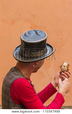 Illusionist With Magician's Hat And Fake Bird During Street Performance