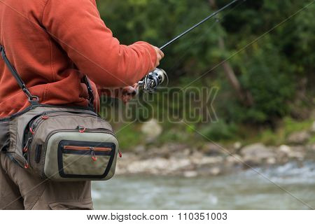 Fisherman on a mountain river catch exotic fish