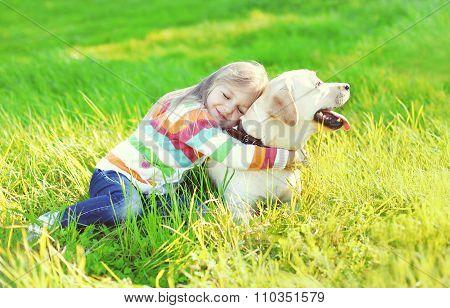 Happy Child Hugging Labrador Retriever Dog On Grass In Summer