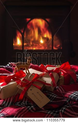 Wrapped Christmas gift boxes by a cosy lit fire