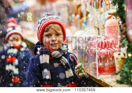Little kid boy with candy cane stand on Christmas market