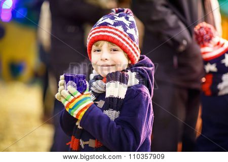 Little kid boy with hot chocolate on Christmas market