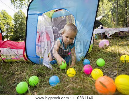 The Boy 1.3 Years Carefully Playing With Colorful Balls In Children Tent On Green Grass  Park.