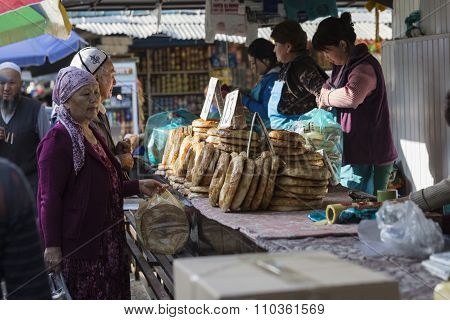 Bishkek, Kyrgyzstan - September 27, 2015 : Woman Selling Asian Style Bread In Local Market.