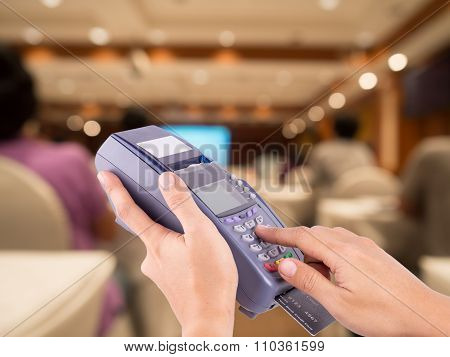 Hand Swiping Credit Card Machine With Blurred People Sitting Rear At The Business Conference In Back