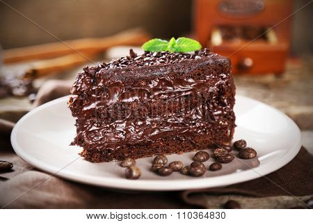 Chocolate cake with chocolate cream and fresh berries on plate, on wooden background