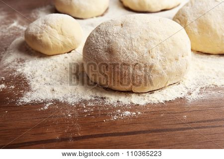 Dough balls for pizza on floured wooden board