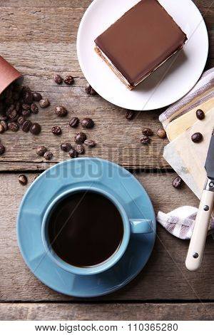 Delicious chocolate brownies and coffee mug on wooden background