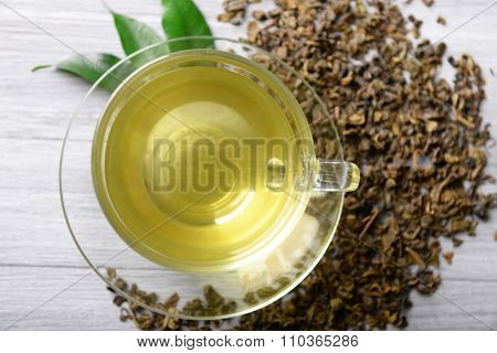 Glass cup of tea with green leaves and scattered tea around on grey wooden background, close up
