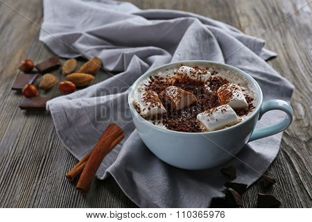 Cup of hot cacao with marshmallow, cinnamon and nuts on blue cotton serviette, close up