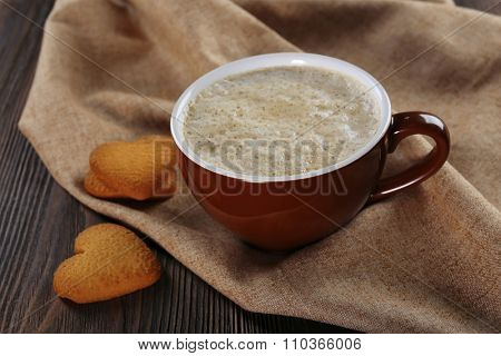 Cup of hot cacao with heart shaped cookies on cotton serviette, close up