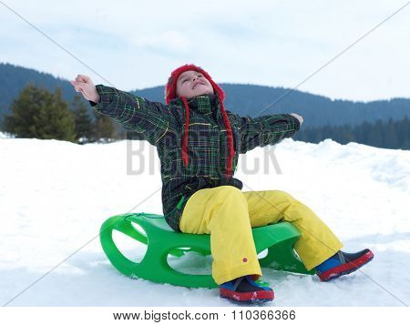 happy young boy have fun on winter vacatioin, sledding children on fresh snow at sunny day outdoor in nature