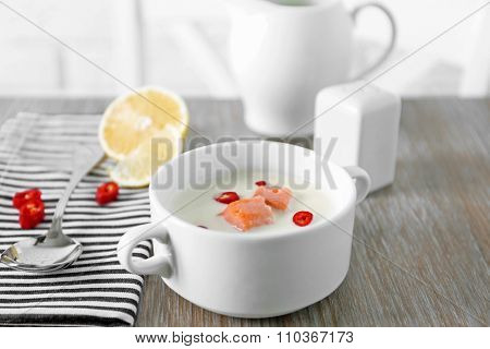 Tasty fish cream soup, lemon, salt and striped cotton serviette on wooden table, close up