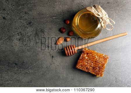 Honeycomb, glass pot with honey and nuts on gray background