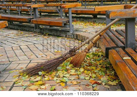 Broom And The Broom Standing Near The Bench Area In The Autumn. Cleaning Street From The Park Autumn