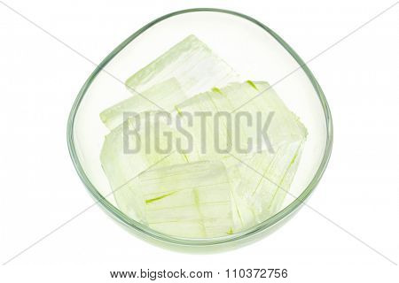 A glass bowl full of freshly picked Aloe vera plant, peeled and cut into pieces isolated on white. Fresh Aloe Vera is natural remedy for sunburn relief and cure many things.