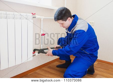 A Plumber Performs The Installation Of Radiator Heating