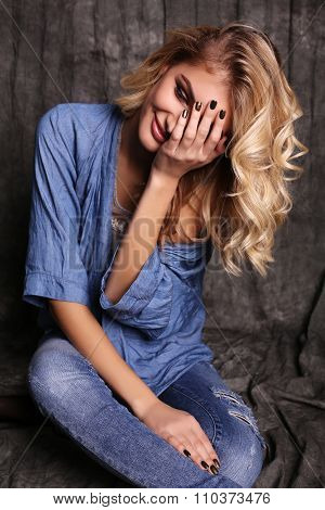 Beautiful Woman With Blond Curly Hair And Evening Makeup,wears Jeans Clothes