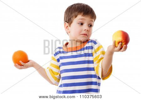 Pensive boy holds a orange and apple