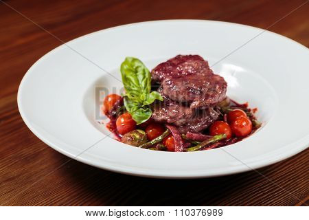 Meat sauce with vegetables in a beautiful exposition on a white plate.