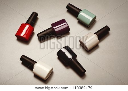 Collection Of Various Nail Polish Bottles On A Vintage Surface