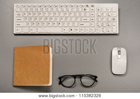 Office Workstation With A Keyboard, Mouse, Notebook And Glasses