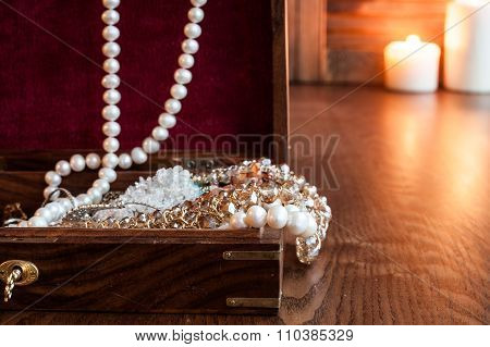 Wooden Box Of Jewels And Jewelry On A Background Of Burning Candles