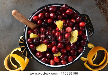 A pot full of fresh cranberries and orange pieces,. High angle view of the traditional Thanksgiving holiday side dish.