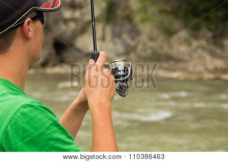 Fisherman on a mountain river catch exotic fish.