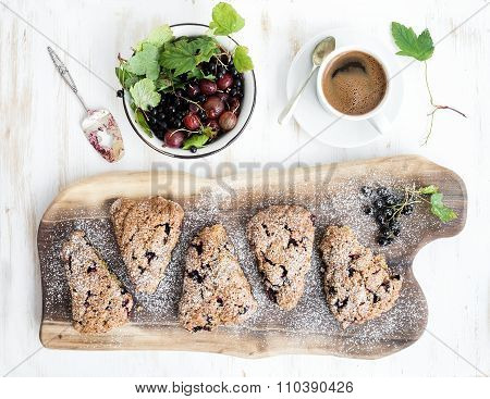 Fresh black-currant scones with coffee and bowl of berries over rustic walnut wood serving board, to