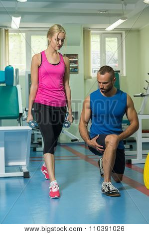Beautiful girl practicing with a trainer at the gym