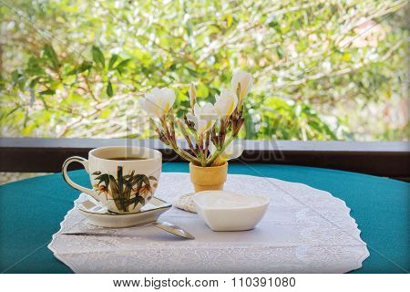 Classic White Cup Of Black Coffee Decorated With Flower And Tree Background
