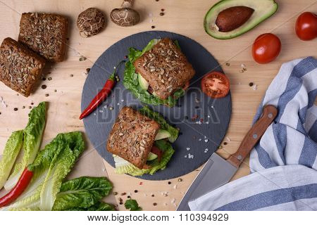Veggie burger with shiitake, falafel and avocado, on wooden background.