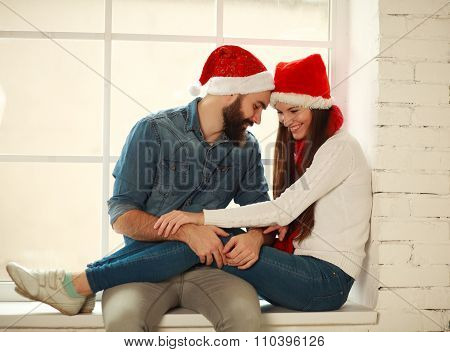 Happy Young Couple In Red Christmas Hats Sitting On The Window