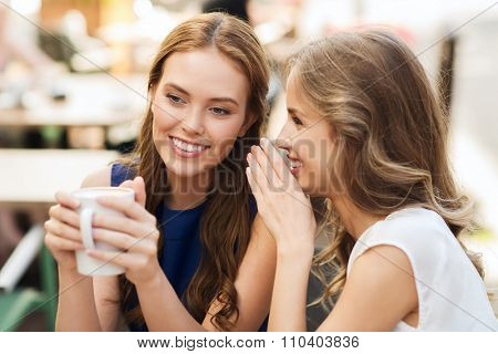 people communication and friendship concept - smiling young women drinking coffee or tea and gossiping at outdoor cafe