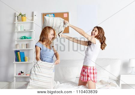friendship, people and pajama party concept - happy friends or teenage girls having fun and pillow fight on bed at home