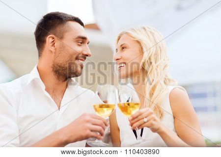 love, dating, people and holidays concept - smiling couple clinking glasses of wine and looking to each other at restaurant lounge or terrace