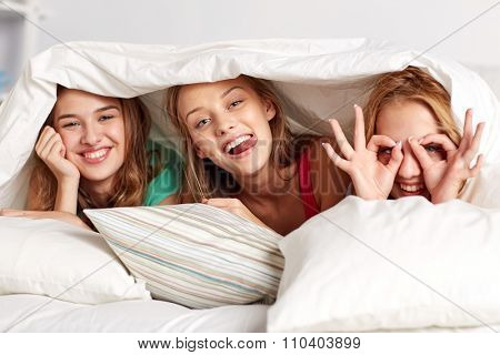friendship, people and pajama party concept - happy friends or teenage girls having fun and lying under blanket with pillows in bed at home
