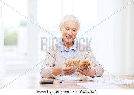 business, savings, annuity insurance, age and people concept - happy senior woman with calculator and bills counting euro money at home