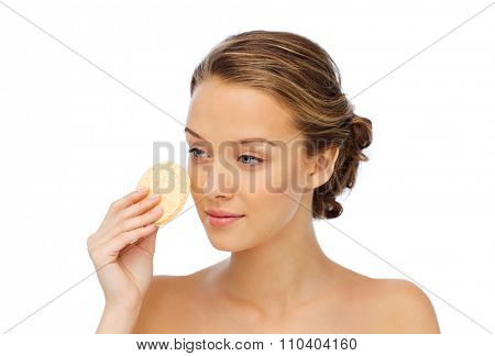 beauty, people and skincare concept - young woman cleaning face with exfoliating sponge