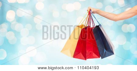 people, consumerism and sale concept - close up of female hand holding shopping bags over blue holidays lights background