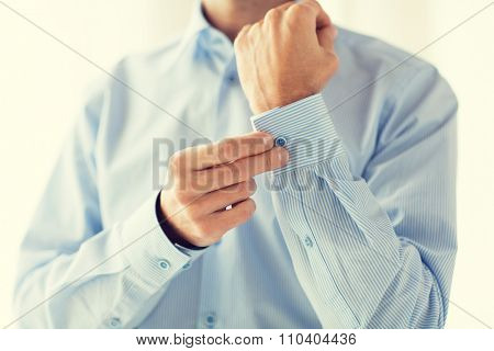 people, business, fashion and clothing concept - close up of man fastening buttons on shirt sleeve at home