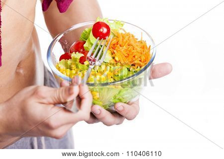 Close-up of a fitness man holding a bowl of salad, isolated on white background