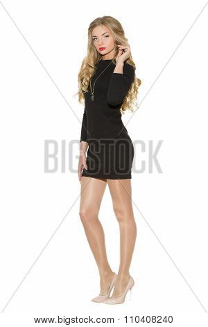 Sexy fashionable curly blonde with bright makeup. Sexual arousal girl in a short dress. Isolated on