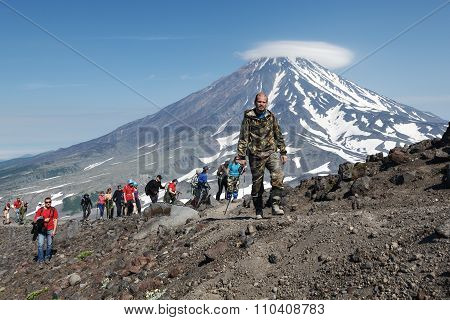 Large Group Of Hikers Climbing To The Top Of Volcano