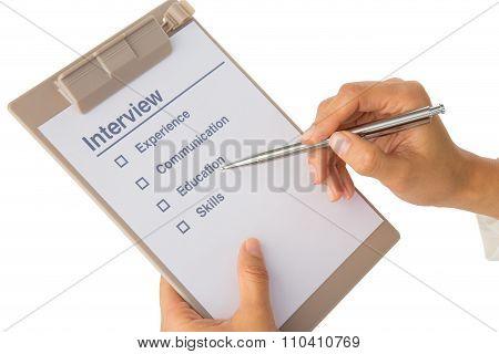 Hand Fills Out Job Interview Checklist