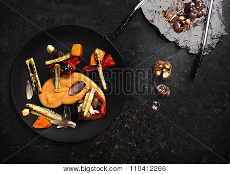 Grilled vegetables in black plate on kitchen table