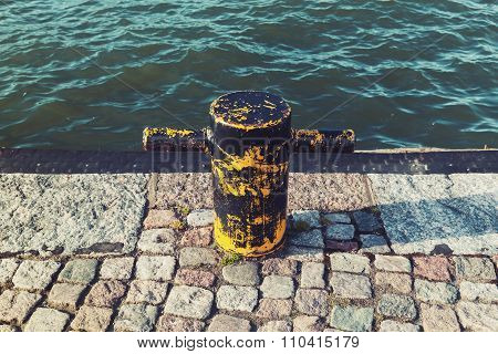 Old Rusted Yellow Mooring Bollard On Stone Pier