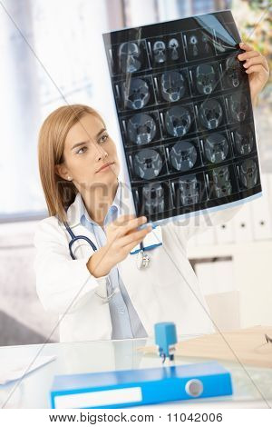 Young Female Doctor Studying X-ray Image